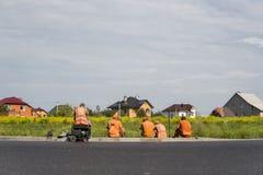 Fyra arbetare som vilar på vägkonstruktionsplatsen med hus bak dem arkivfoto
