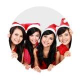 Fyra asiatiska kvinnor med den julsanta hatten i cirkel Arkivbild