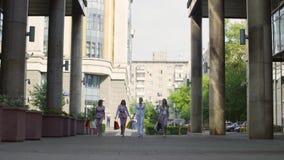 Fyra attraktiva affärskvinnor som går i staden lager videofilmer