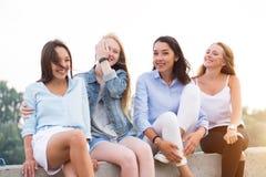 Fyra attraktiva kvinnor i sommarkläder som sitter på den konkreta gränsen nära floden, når studing fotografering för bildbyråer
