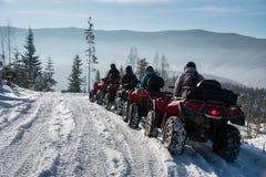 Fyra ATV-ryttare på av-väg kvadrat cyklar i vinterbergen Arkivfoto