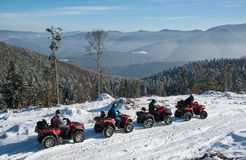 Fyra ATV-ryttare på av-väg kvadrat cyklar på insnöad vinter Royaltyfria Bilder