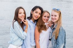 Fyra bästa flickvänner som tillsammans ser kameran folk livsstil, kamratskap, kallbegrepp Ung gladlynt studentflicka arkivbilder
