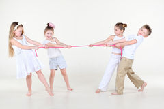 Fyra barn i vitkläder spänner det rosa repet för hårt Arkivfoton