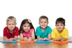 Fyra barn med böcker Royaltyfri Foto