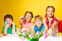 Fyra barn som rymmer färgade påskägg Arkivfoto