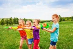 Fyra barn som spelar med vattenvapen Royaltyfri Foto
