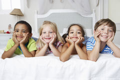 Fyra barn som spelar på säng tillsammans Arkivfoto