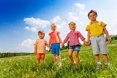 Fyra barn som tillsammans rymmer händer och anseende Royaltyfri Fotografi