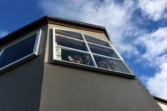 Fyra barn som vinkar farväl från ett fönster Royaltyfri Fotografi