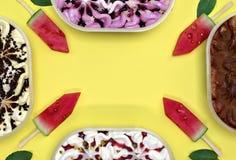 Fyra behållare med kulör glass och vattenmelon med pinnar arkivfoto