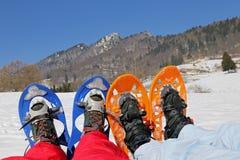 Fyra ben med snöskor för utfärder på snön Royaltyfri Foto