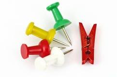 Fyra ben och en röd miniatyrklädnypa Arkivfoto