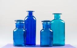 Fyra blåa flaskor och deras glass stordia Fotografering för Bildbyråer