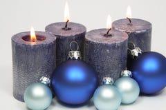 Fyra blåa stearinljus och blåa bollar för julträd Arkivfoton