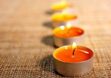Fyra brännande orange stearinljus Royaltyfri Fotografi