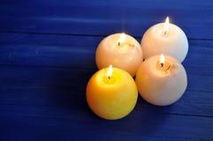 Fyra brännande sfäriska stearinljus på tabellen royaltyfri bild