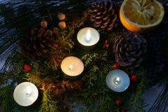 Fyra brännande stearinljus bland julgarneringar Royaltyfria Bilder