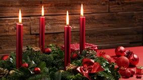 Fyra brinnande röda stearinljus på en traditionell adventkrans med festlig garnering arkivfilmer