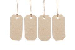 Fyra bruna etiketter som hänger på rep Royaltyfri Foto
