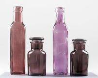 Fyra bruna och violetflaskor och deras glass stordia Royaltyfri Fotografi