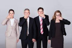 Fyra businesspeople som göra en gest för tystnad Royaltyfria Foton