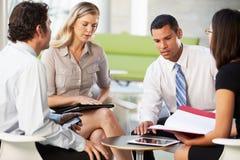 Fyra Businesspeople som har möte i modernt kontor royaltyfri foto