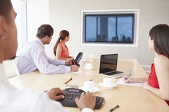 Fyra Businesspeople som har videokonferens i styrelse Arkivbild