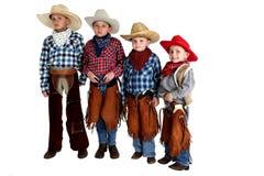 Fyra cowboybröder som står bärande hattar, och killar Arkivbilder