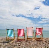 Fyra Deckchairs på ett Pebble Beach fotografering för bildbyråer