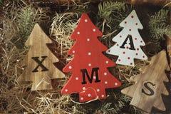 Fyra dekorativa träjulgranar med sned bokstäver xmas och julprydnader Top beskådar arkivbild