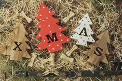 Fyra dekorativa träjulgranar med sned bokstäver xmas och läckerhet i form av små ben för husdjur Top beskådar arkivbilder