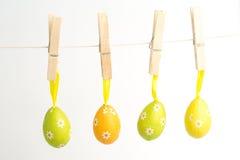 Fyra easter ägg som hänger från en fodra Royaltyfri Foto