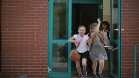 Fyra elever har gyckel efter skolakurser De bär skolalikformign Skolabyggnad är på bakgrund arkivfilmer