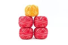 Fyra färgade sömnadtrådar i rad på en vit bakgrund Röda och gula trådar Royaltyfria Foton