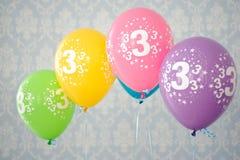 Fyra färgrika ballonger med nummer 3 Arkivfoton