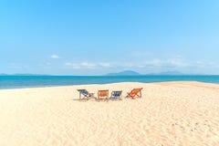 Fyra färgrika deckchairs på stranden Fotografering för Bildbyråer