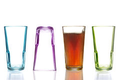 Fyra färgrika dricka exponeringsglas, ett med cola Arkivbild