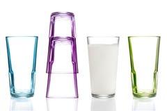 Fyra färgrika dricka exponeringsglas, ett med mjölkar Royaltyfri Bild