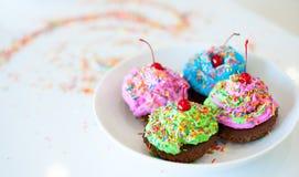 Fyra färgrika ljusa muffin med kräm och bestänkande ligger på ett uppläggningsfat Royaltyfria Foton