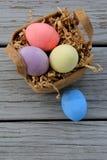 Fyra färgrika påskägg och en nätt liten korg Arkivbild