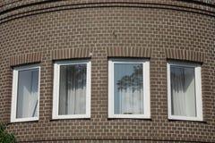 Fyra fönster av en tegelstenbyggnad Royaltyfri Foto