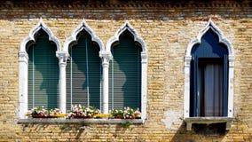 Fyra fönster i ärke- form och forntida förfalltegelstenvägg Royaltyfri Bild