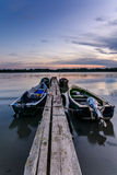 Fyra förtöjde fartyg på solnedgången nära en träpir Vertikal sikt av Royaltyfri Foto
