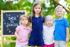 Fyra förtjusande lilla ungar går tillbaka till skolan Arkivbild