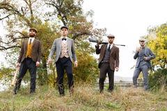 Fyra farliga gangster som röker och rymmer gevär, slagträn och knivar i gatan retro utomhus Arkivfoto