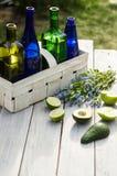 Fyra flaskor av drinkar i den vita korgen och frukter på en vit tabell Arkivbilder