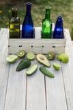 Fyra flaskor av drinkar i en vit korg och frukter på den vita tabellen Arkivfoto