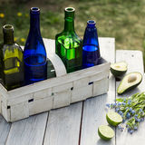 Fyra flaskor av drinkar i en vit korg och frukter på den vita tabellen Arkivbilder