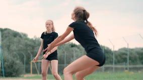 Fyra flickor som spelar volleyboll p? stranden Strandvolleyboll som ?r netto, kvinnor i bikinier Plan tecknad filmillustration st arkivfilmer